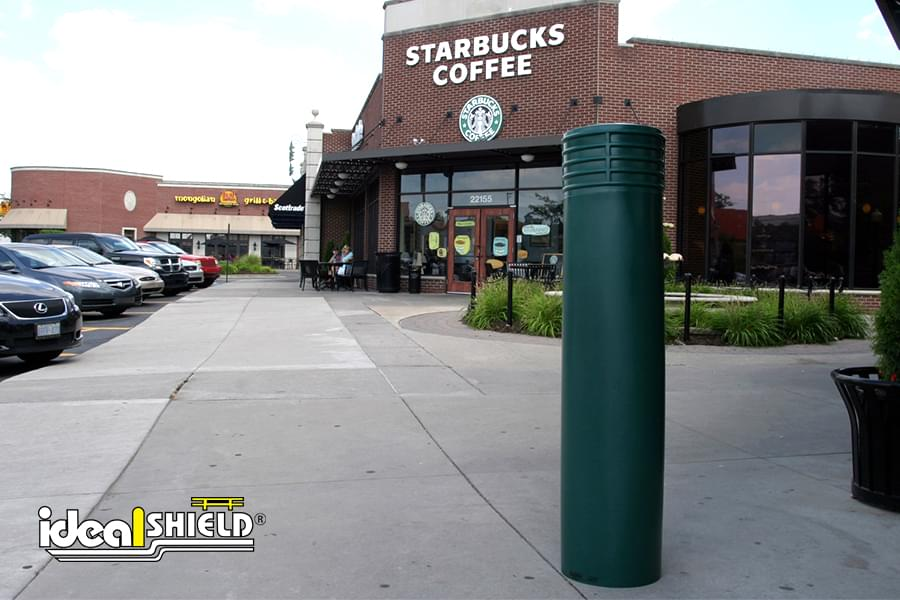 "Ideal Shield's 10"" green Cinco Bollard Cover outside of a Starbucks"