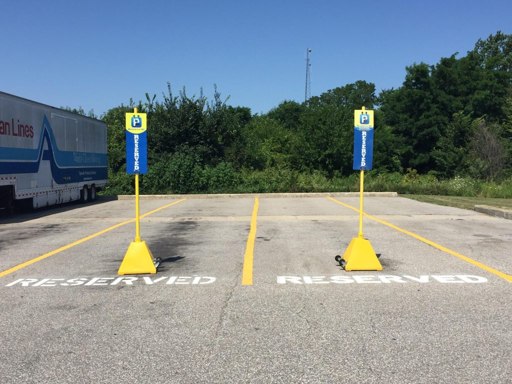 Ideal Shield's yellow portable Sign Bases used for reserved parking spots