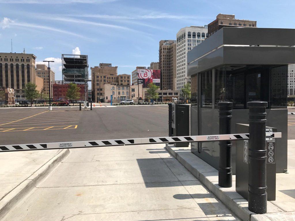 Ideal Shield's black Metro Decorative Bollard Covers guarding a parking lot gate entrance