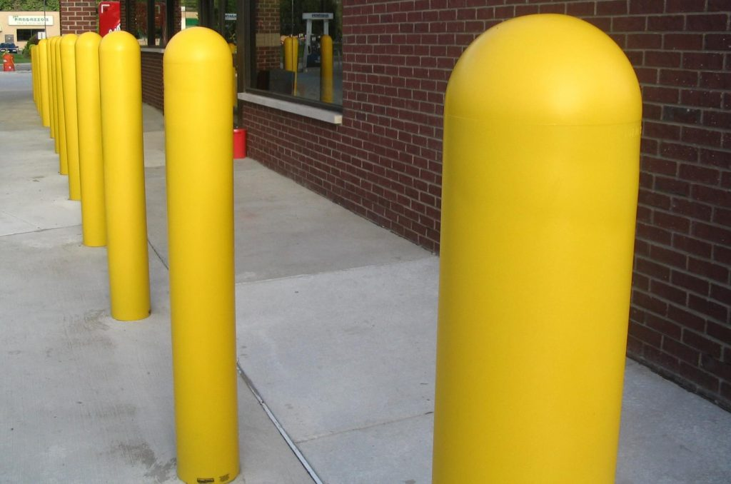 Ideal Shield's yellow bollard covers guarding a storefront