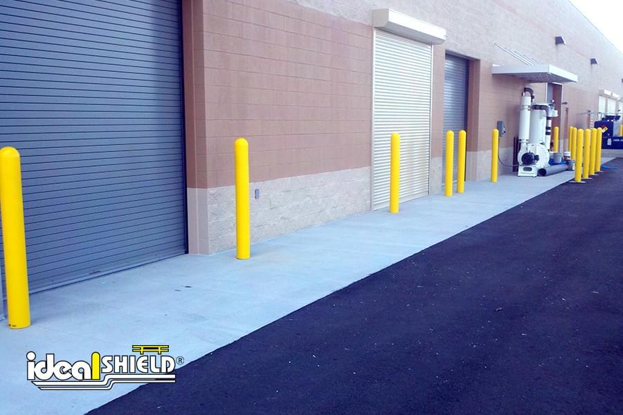 Ideal Shield's yellow plastic Bollard Covers guarding garage doors