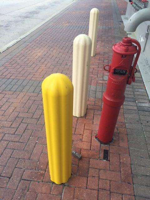 Yellow bollard cover alongside faded yellow bollard covers