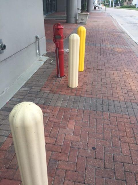 Yellow bollard cover alongside two faded yellow bollard covers