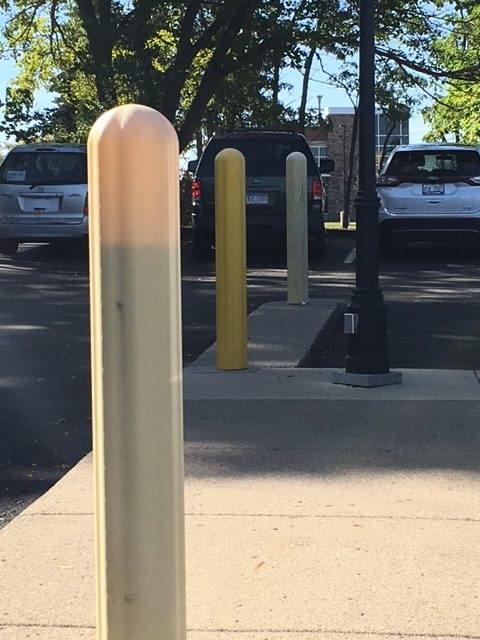 Yellow bollard cover between two faded yellow bollard covers