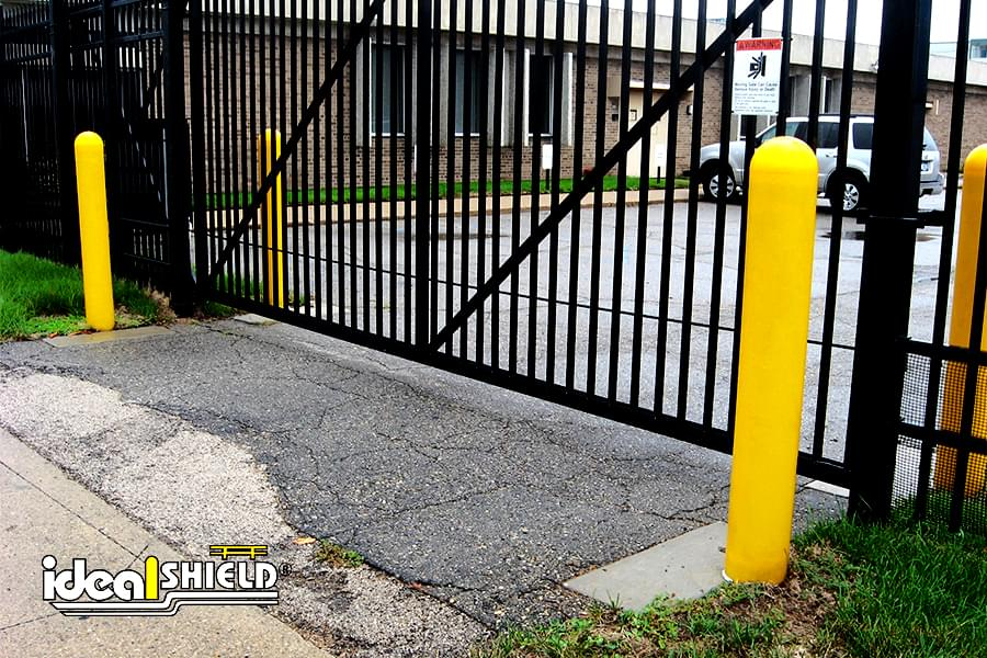 Ideal Shield's yellow plastic Bollard Covers guarding the entrance gate at a storage facility