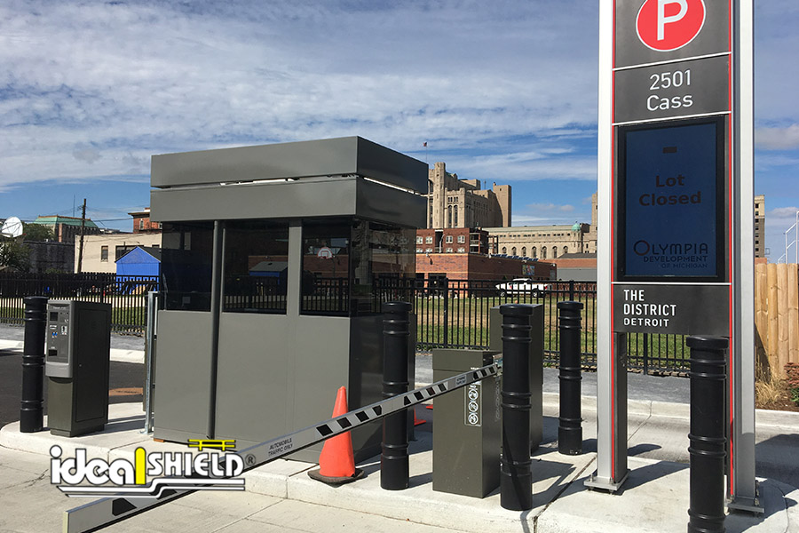 Ideal Shield's black Metro Decorative Bollard Covers guarding a surface parking lot kiosk
